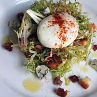 FRISEE SALAD WITH POACHED EGGS, BACON LARDON, BLUE CHEESE